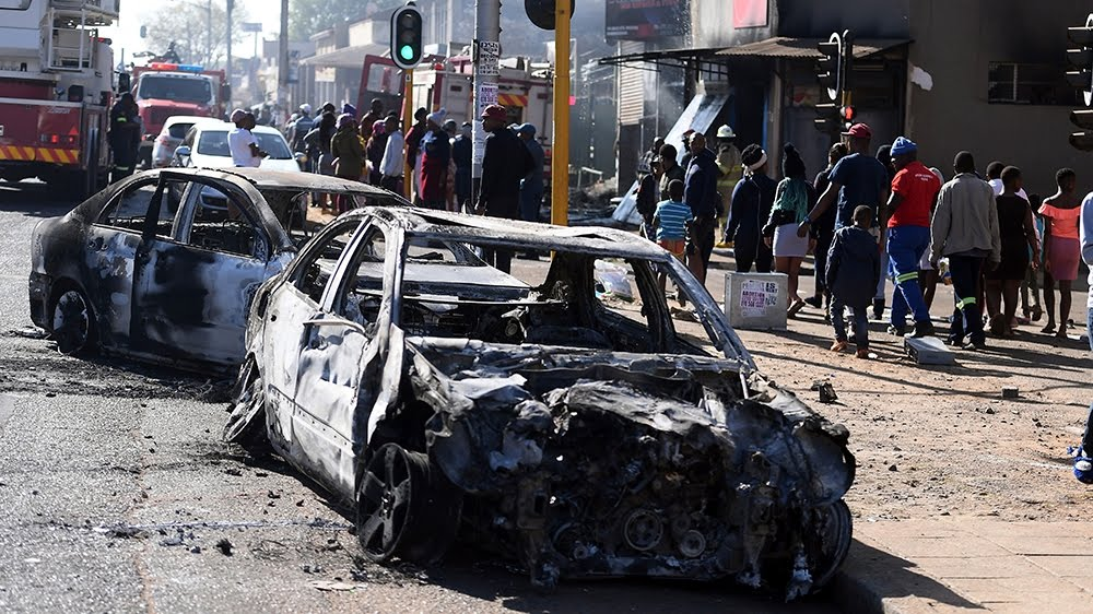 Pedestrians pass burnt out cars on the side of a street on the outskirts of Johannesburg Monday Sept. 2, 2019. Police had earlier fired rubber bullets as they struggled to stop looters who targeted bu