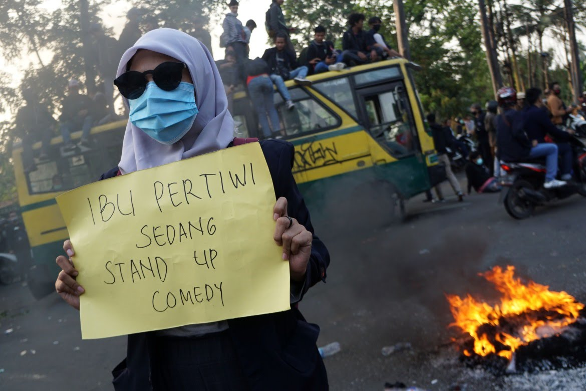 """A student holds a sign reading """"the motherland is on stand-up comedy"""" during protests in Tangerang. [Fajrin Raharjo/AFP]"""