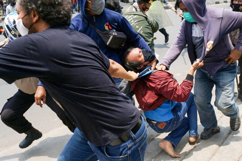 Plain-clothes police detain a protester in Tangerang. [Fajrin Raharjo/AFP]
