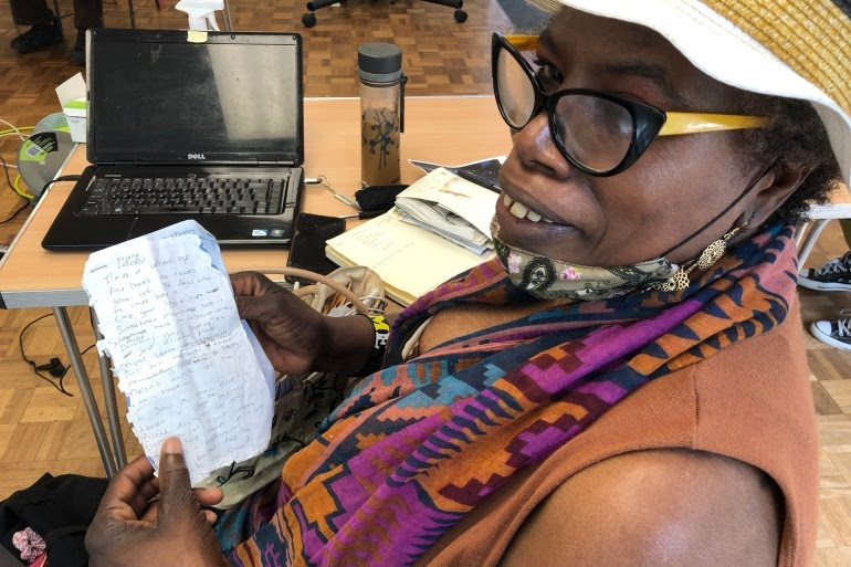 Gloria Brown, 66, shows a poem she has written, in front of her laptop at CatBytes, a social enterprise in South London which supports older people who need to develop digital skills [Amandas Ong/Al Jazeera]