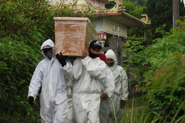 Grave diggers carry a coffin for burial at a cemetery for people who've died from coronavirus in Bandung [Timur Matahari/AFP]